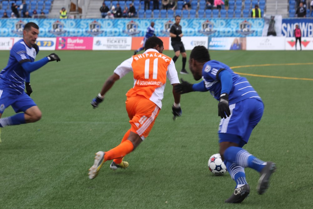 Tiyi Shipalane runs past an FC Edmonton defender during the two teams' spring matchup. (Photo: FC Edmonton)